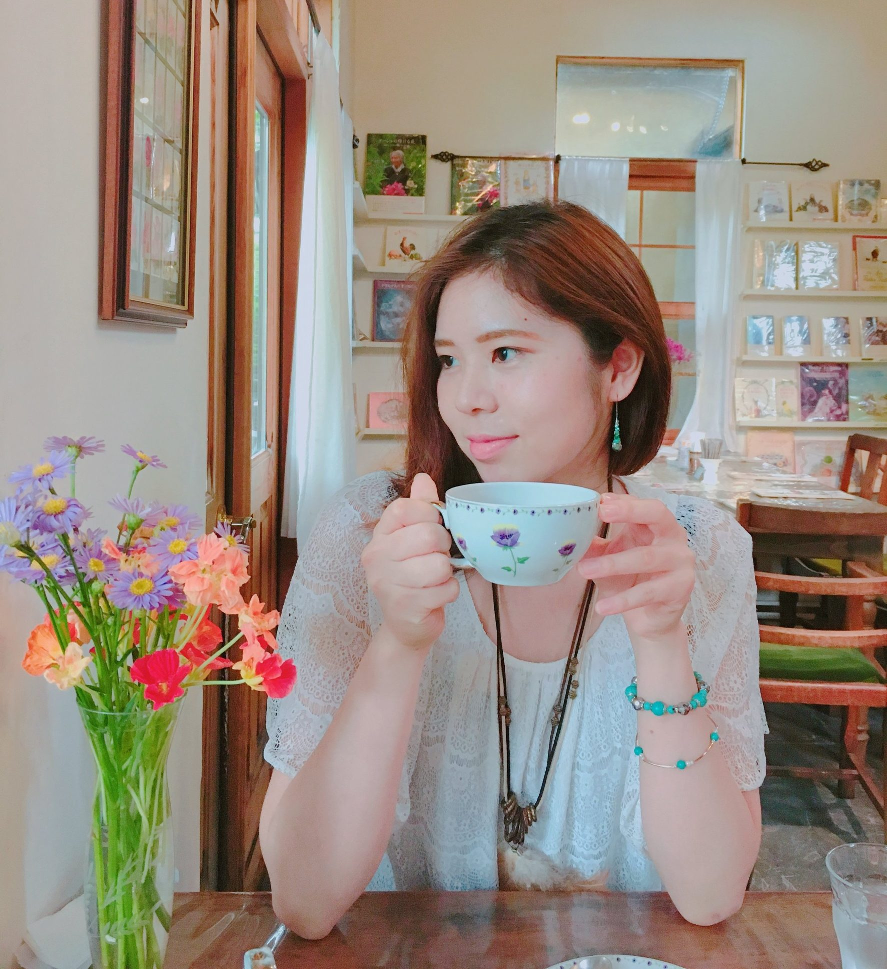 紅茶のカップを持った女と机の上に花瓶と花
